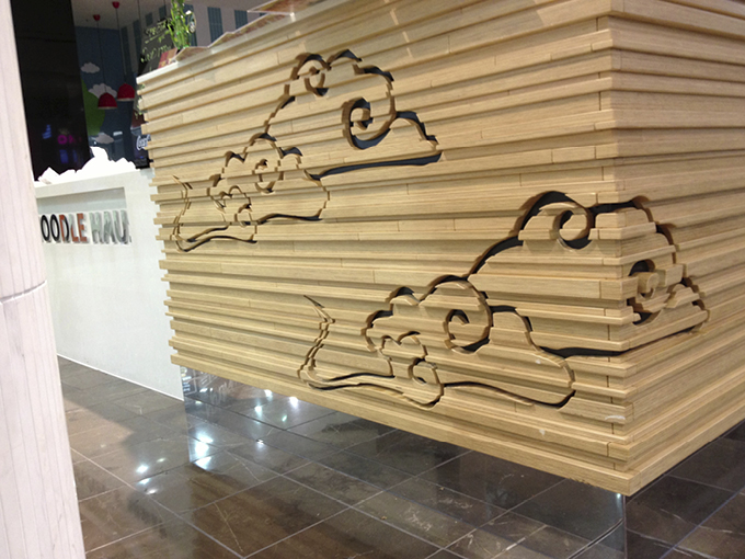 Noodle Haus shop design - detail of stacked plywood and routered cloud motif